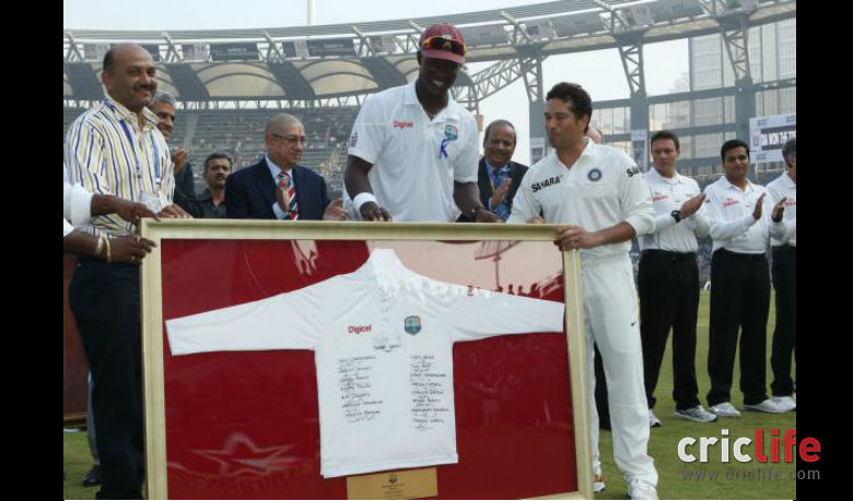 West Indies skipper Darren Sammy presents a t-shirt with signatures of his team members to the maestro before the start of play.
