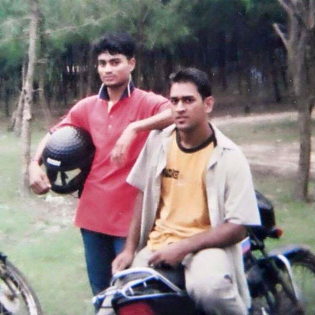 Young MS Dhoni sitting on a bike with short hair - Cricket Country