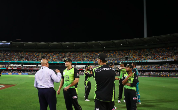 Sydney Thunder players speak to a match official as they wait for the light tower to turn on.